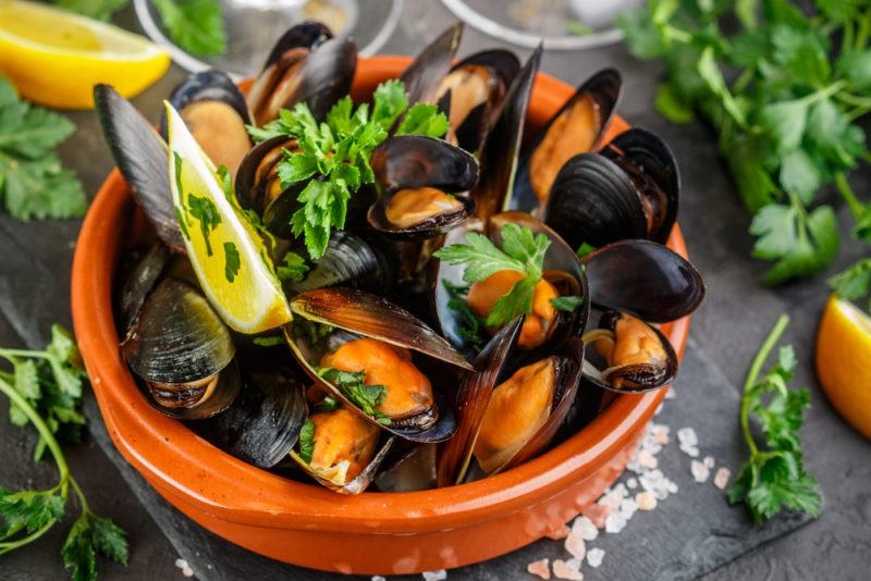 An orange bowl with mussels and parsley, where the orange from the mussels can be clearly seen