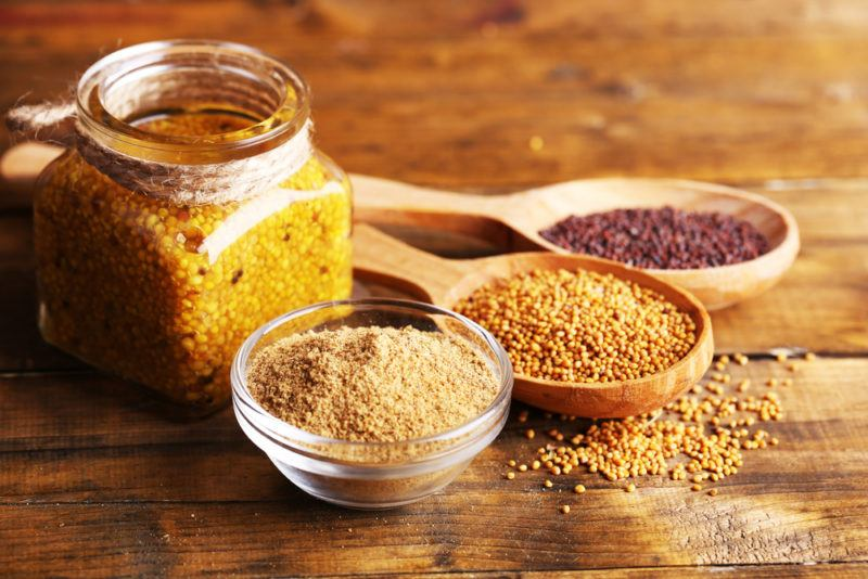 A small glass bowl of mustard powder, a wooden spoon of red mustard seeds, a wooden spoon of yellow mustard seeds and a jar of mustard