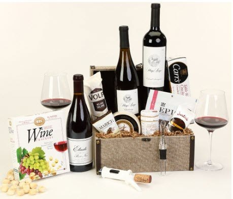 Basket against a light background, with various bottles of wine, snacks and wine accessories