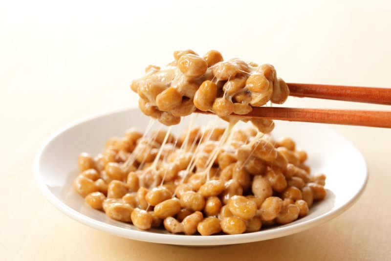A white bowl of natto with chopsticks