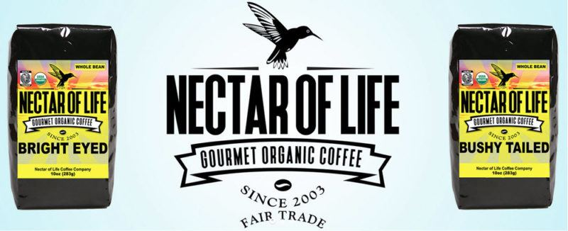 Two black bags of coffee from Nectar of Life, with the company's logo in the center
