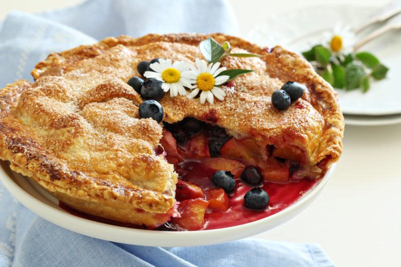 A white dish a nectarine and blueberry pie on a blue cloth