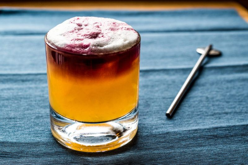 A two-toned New York sour in a glass on a blue table