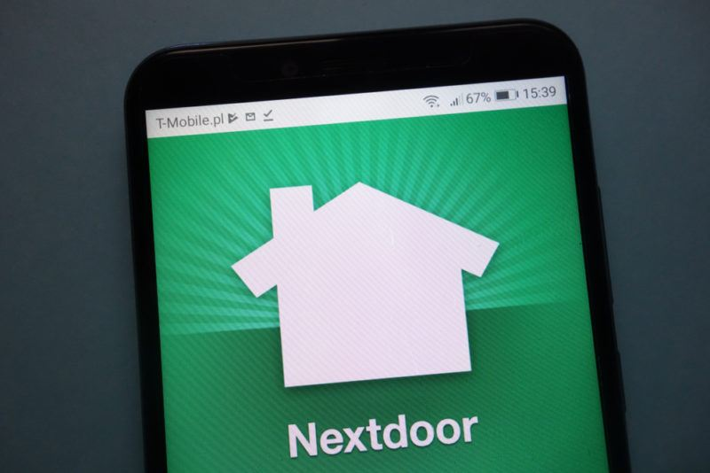 The Nextdoor app with a green background on a cellphone