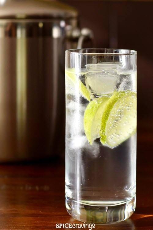 A tall glass with white sparkling liquid, ice and lime slices.