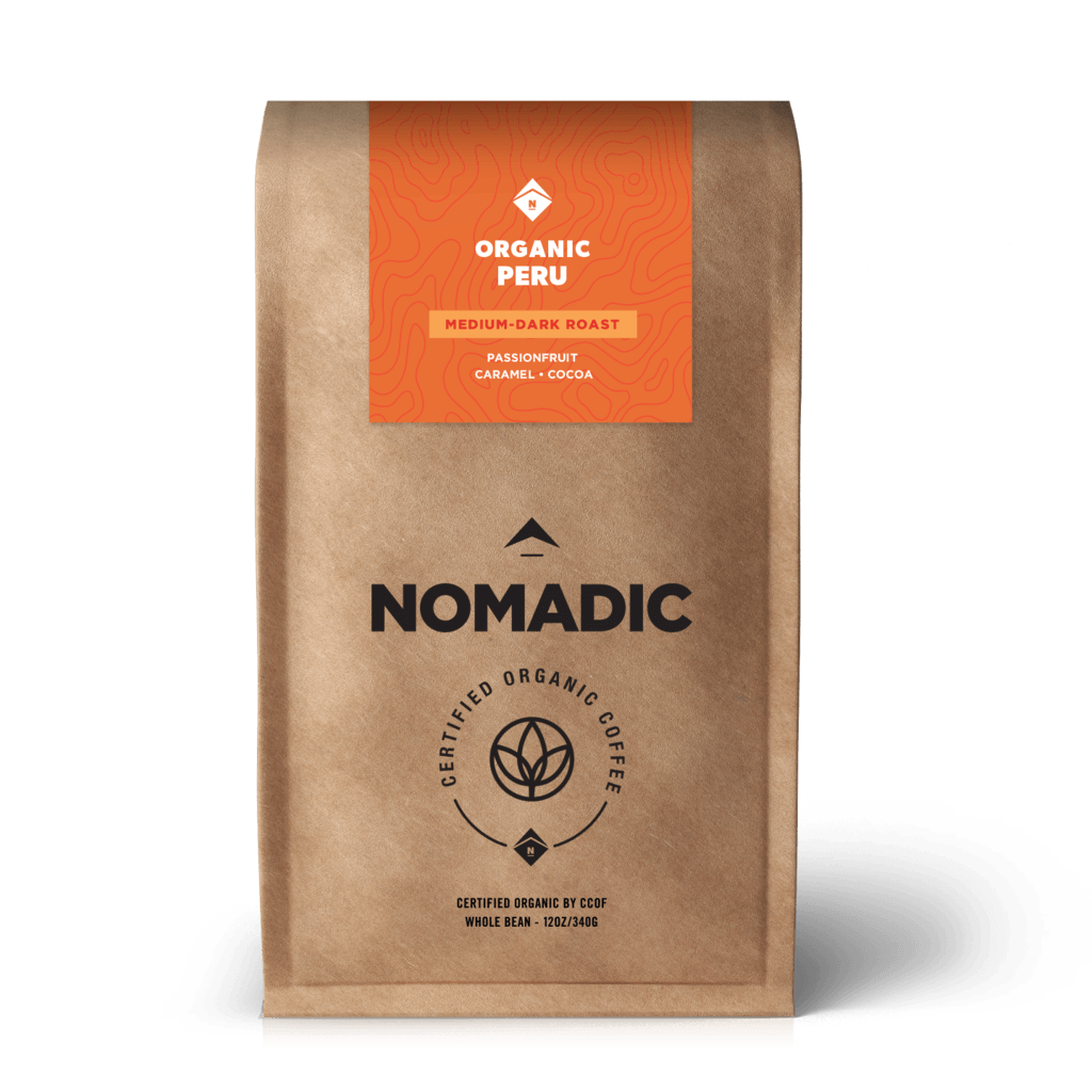 A one pound brown bag of coffee with an orange sticker on the top that says organic Peru, medium dark roast, passion fruit. caramel, cocoa.  Below the orange sticker in black font Nomadic. certified organic coffee