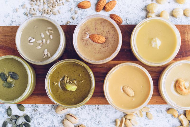 Top down image of various types of nut butters with the associated nut or seed on top