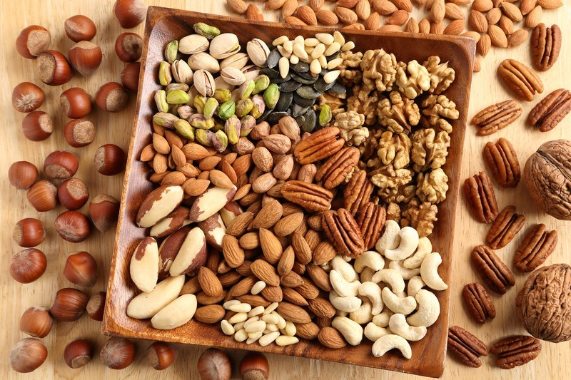 A square wooden dish filled with a variety of nuts is surrounded by several types of loose nuts on a wooden table.