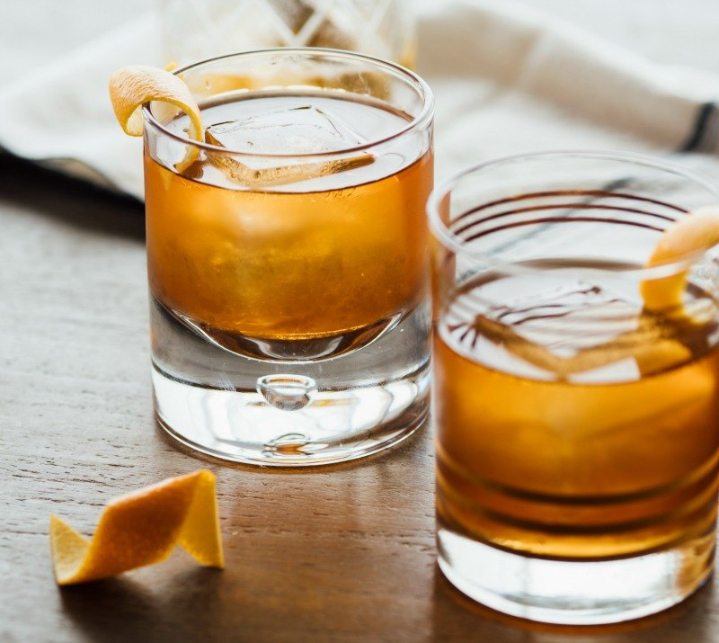 Two old fashions sitting on a wood table each with a an orage twist and an orange twist sitting in front