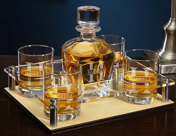 A tray on a wooden table containing four whiskey glasses and a decanter, all engraved.