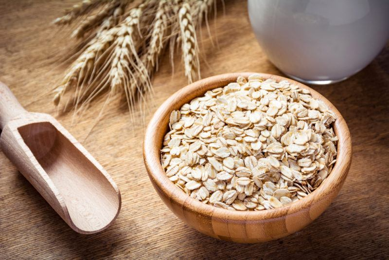 A bowl of oats next to a spoon and grains