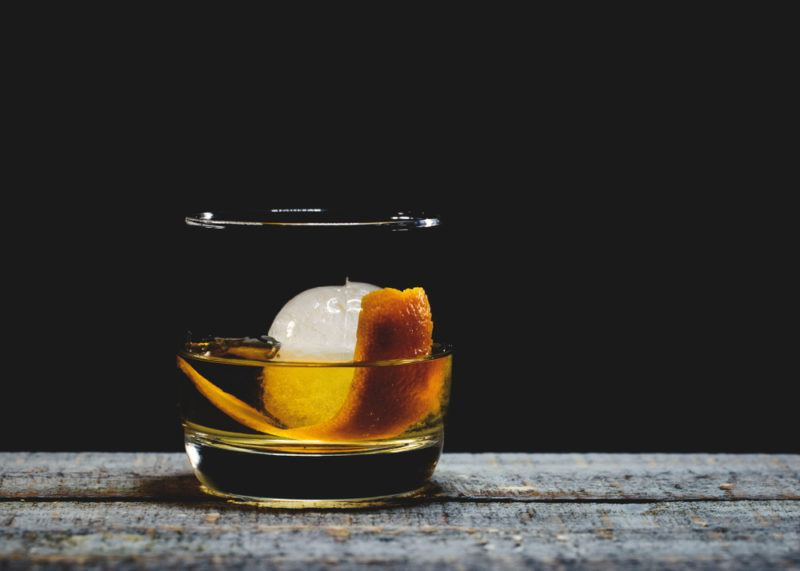 A glass of old fashioned cocktail isolated on a black background