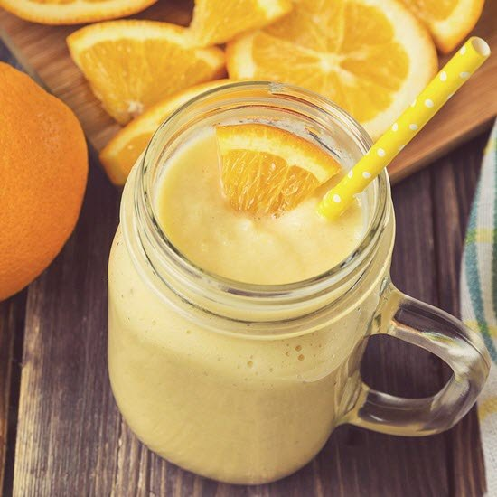 A top-down image of an orange smoothie in a mason jar