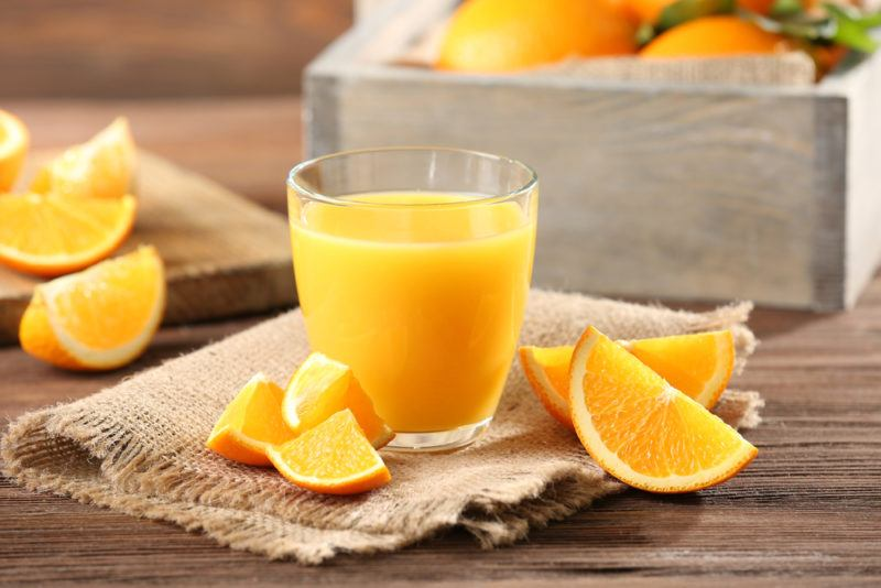 A glass of orange juice on a table with orange wedges scattered around