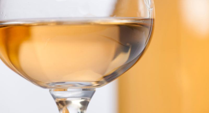 A glass of orange muscat wine with a bottle out-of-focus in the background