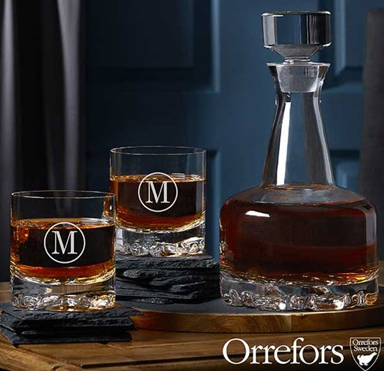A whiskey decanter and glasses on various slate coasters