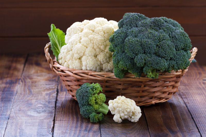 A basket containing raw cauliflower and raw broccoli