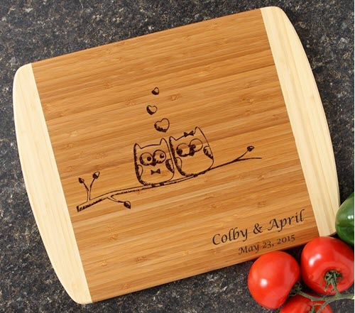 Two-tone cutting board with two owls on a branch.
