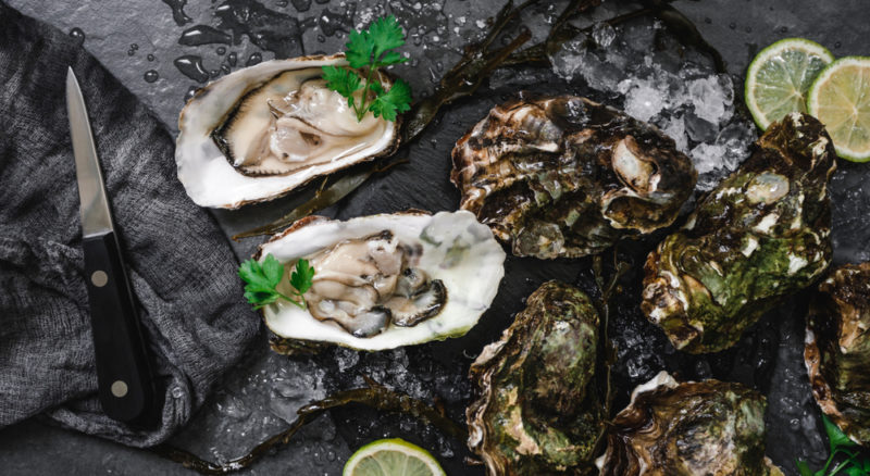 A selection of oysters on a black board with a knife and lime slices