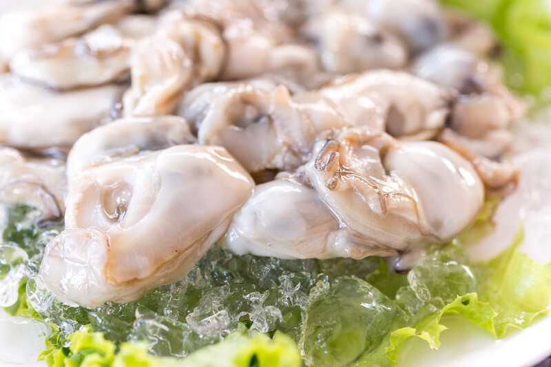 Several grayish pink oysters rest on a bed of greens.
