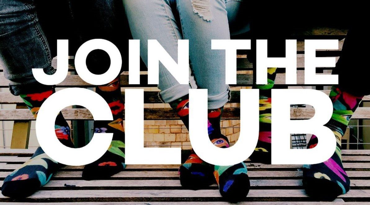 Three people sitting on the back of a bench with colorful socks and no shoes across the photo in white font it says Join The Club