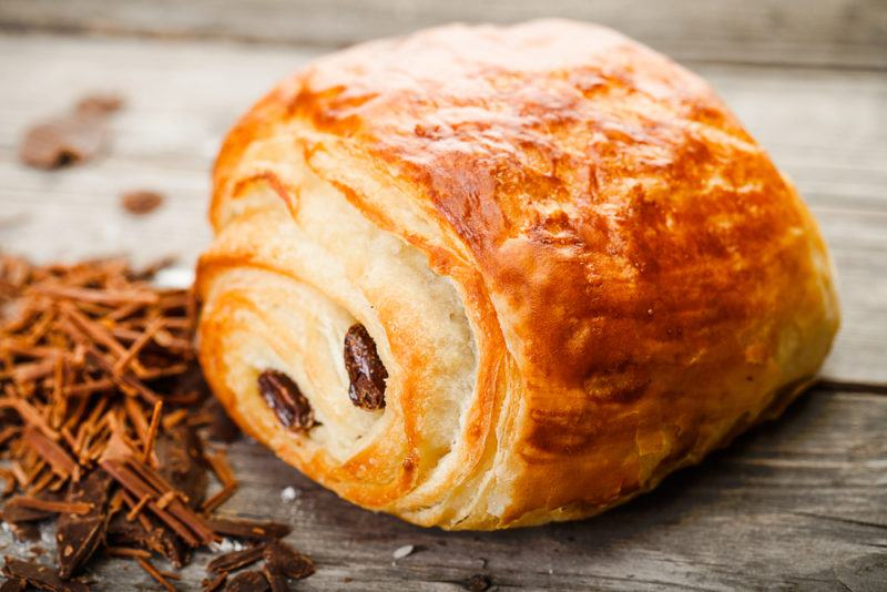 A freshly cooked pain au chocolate on a table