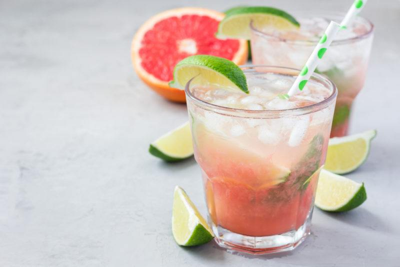 A paloma cocktail with grapefruit soda and lime wedges