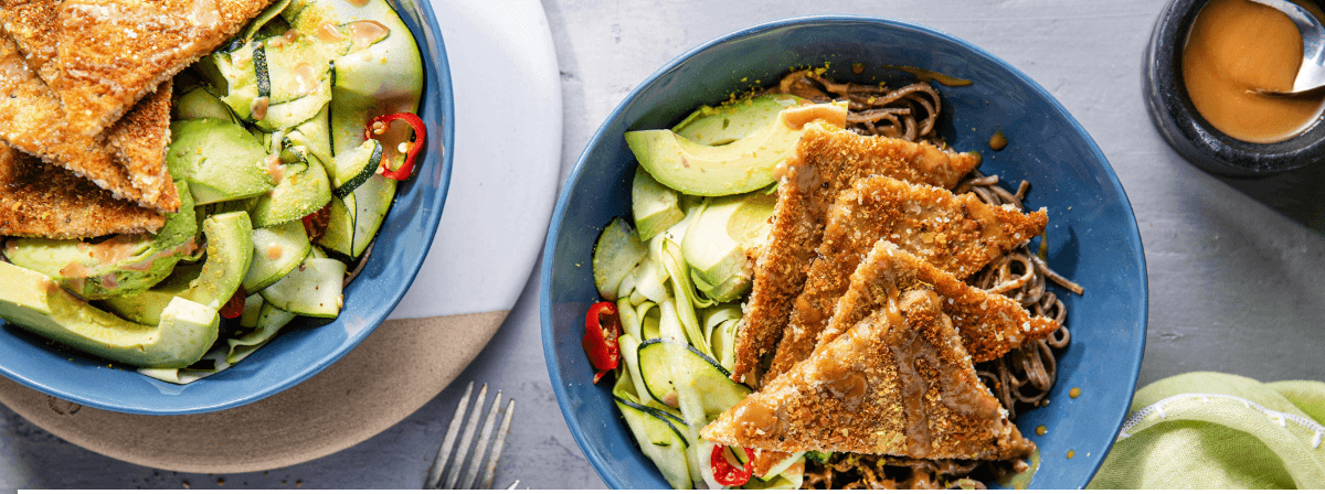 Two Panko-Crusted Tempeh bowls with soba noodles and avocado and chili peppers and cucumbers.  In the upper left corner is a peanut sauce and lower right corner a green cloth napkin, and fork tines poking up at the bottom of the picture in between the two bowls