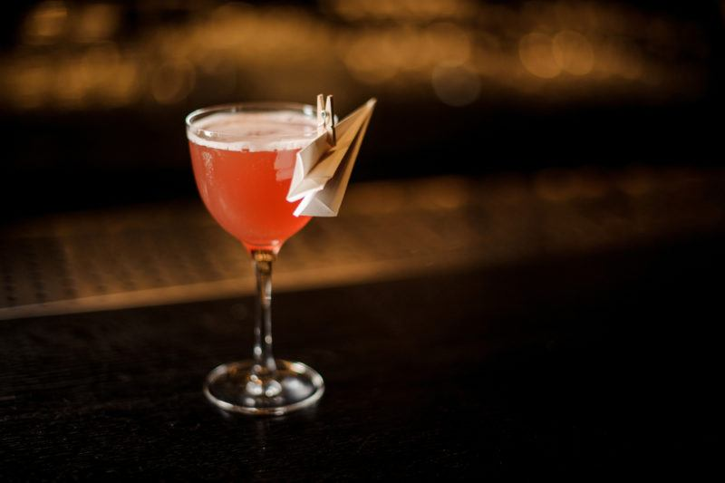 An orange paper plane cocktail with a paper plane attached to the outside