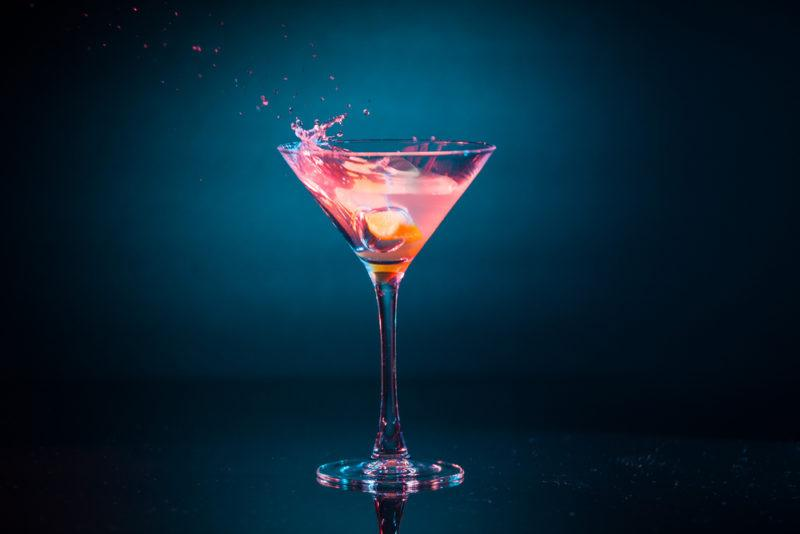 A pink passion cocktail against a dark background