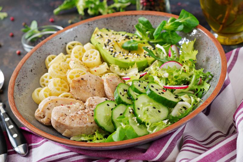 A bowl with pasta, avocado and other healthy ingredients