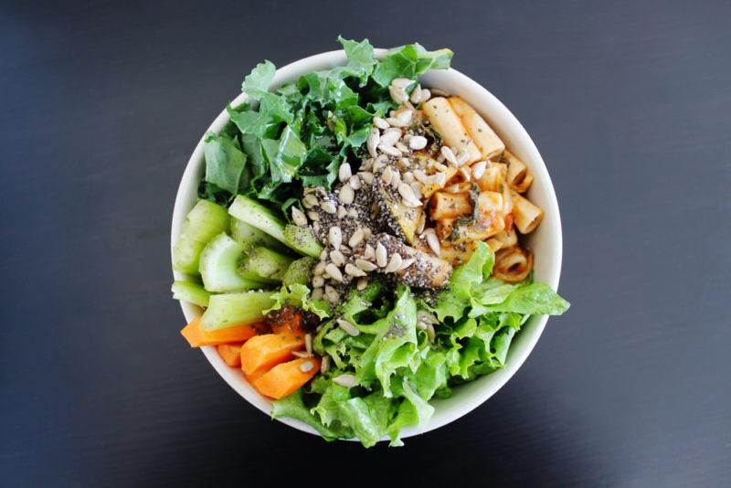 A white bowl with pasta salad and various greens