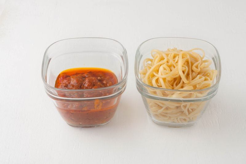 A container of pasta and another of sauce
