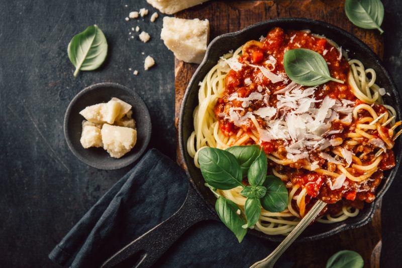 A cast iron pan with pasta and marinara sauce and parmesan