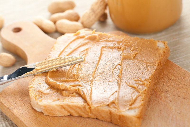 Peanut butter on white bread sitting on a wooden cutting board, with a butter knife leaning against the bread.  A jar of peanut butter and shelled peanuts are in the background