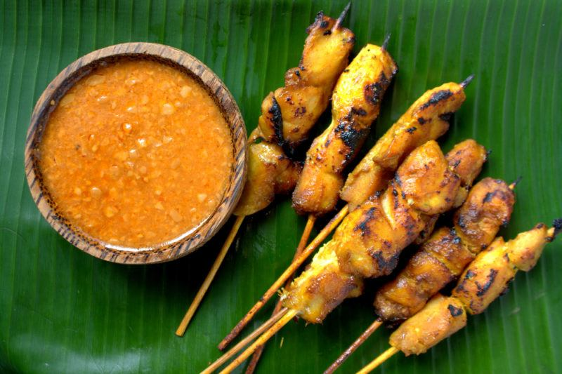 Half a dozen or so kebabs with satay chicken next to peanut sauce on a large green leaf