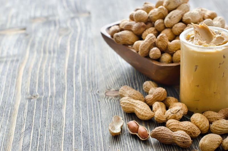 A brown bowl of peanuts, with peanuts on a table and a jar of peanut butter