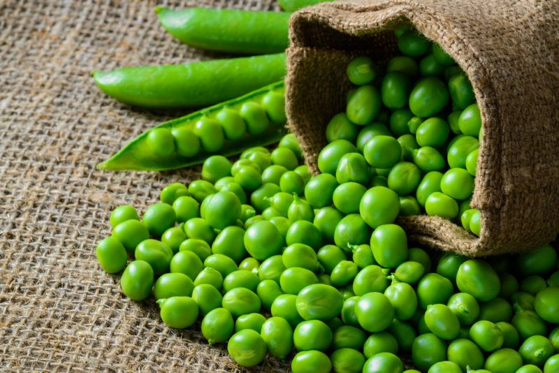 A bag of fresh peas spilling out onto the table