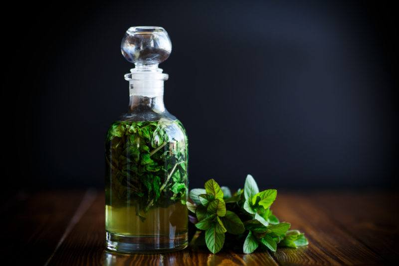 A bottle of peppermint syrup and some peppermint leaves against a dark background