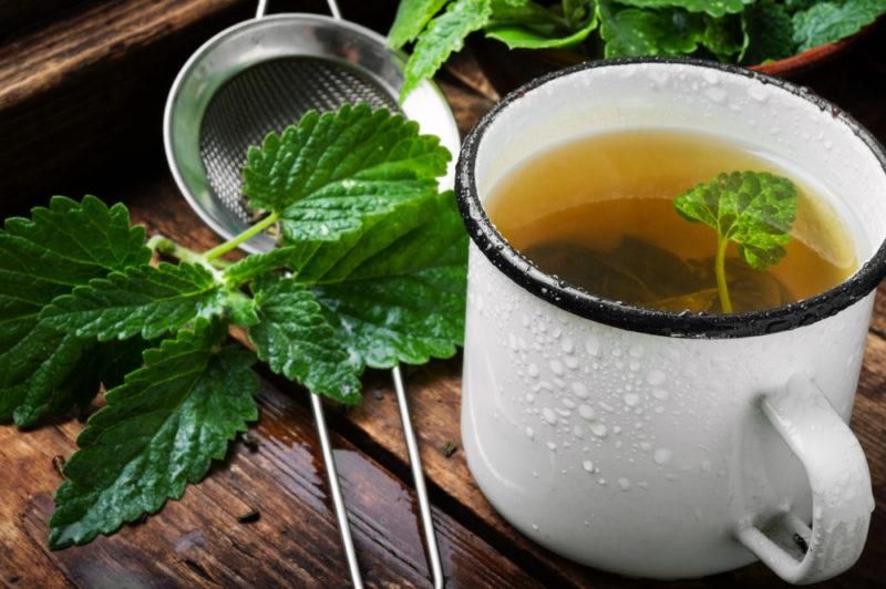 A white mug of peppermint tea with peppermint leaves and a strainer