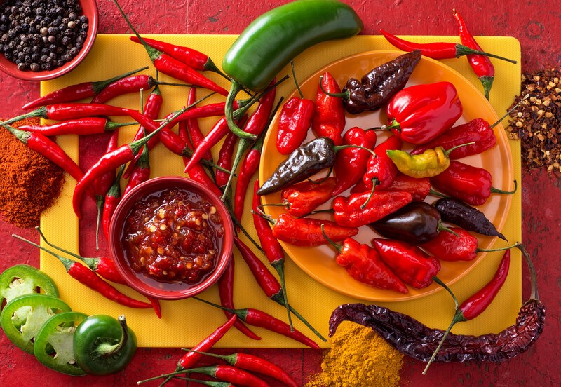 This photo shows an overhead view of a yellow cutting board topped with and surrounded by several types of hot peppers in red and green, as well as a bowl of pepper sauce, a bowl of peppercorns, and three piles of pepper flakes and powders on a red tabletop.