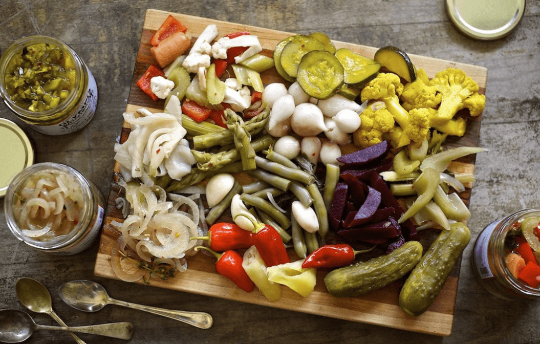 Wooden cutting board with an array of pickled vegetables like onions, asparagus, mini peppers, garlic, pearl onion, cauliflower, cucumbers, beets, and green beans.  3 jars of pickles surrounding the cutting board and three silver spoons in the lower left corner