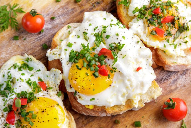 Three pieces of toast with eggs and herbs