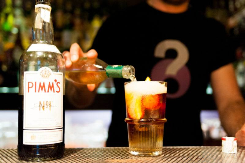 A bottle of Pimms with a cocktail