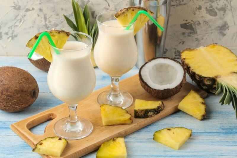 A wooden board with two pina colada cocktails and pineapple wedges, with pineapple and coconut on the table
