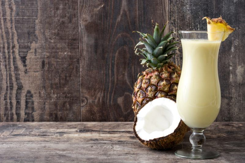 A pina colada, coconut and pineapple on a wooden table