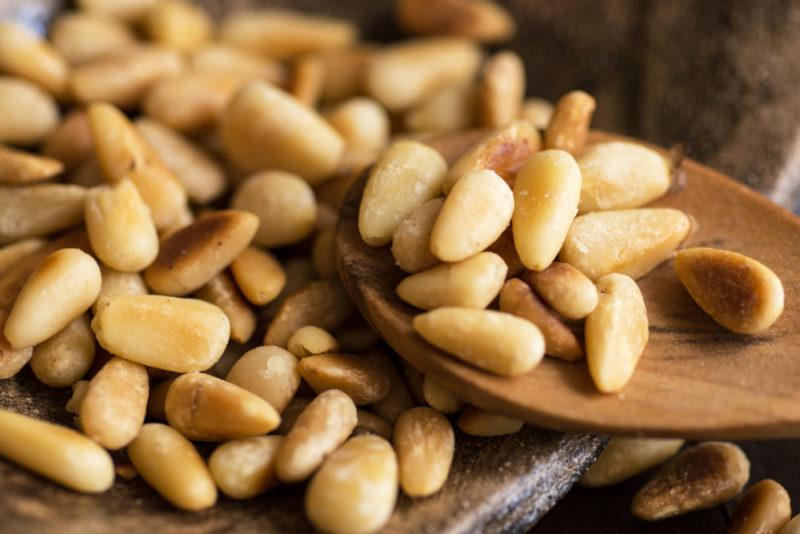 Pine nuts on some type of board with some being lifted out and placed on a spoon