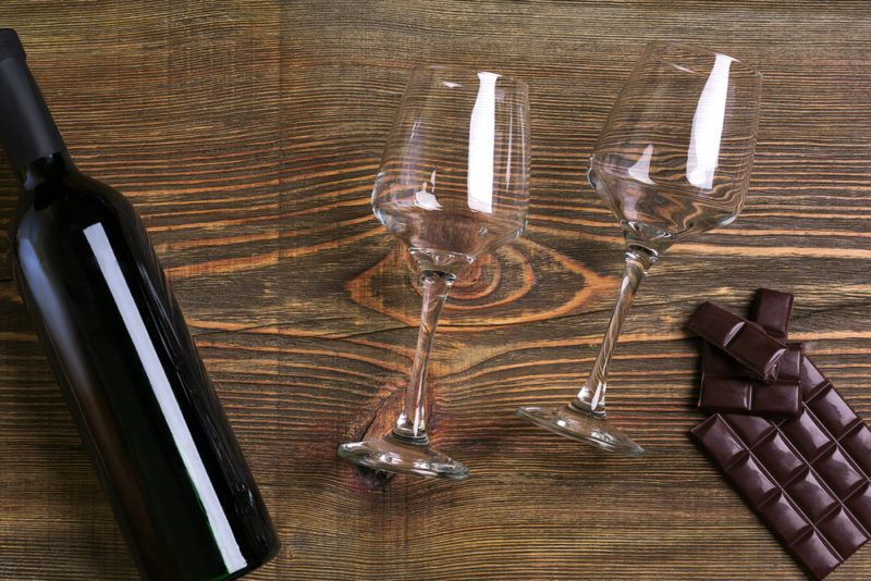 A bottle of pinot noir, two glasses, and some dark chocolate