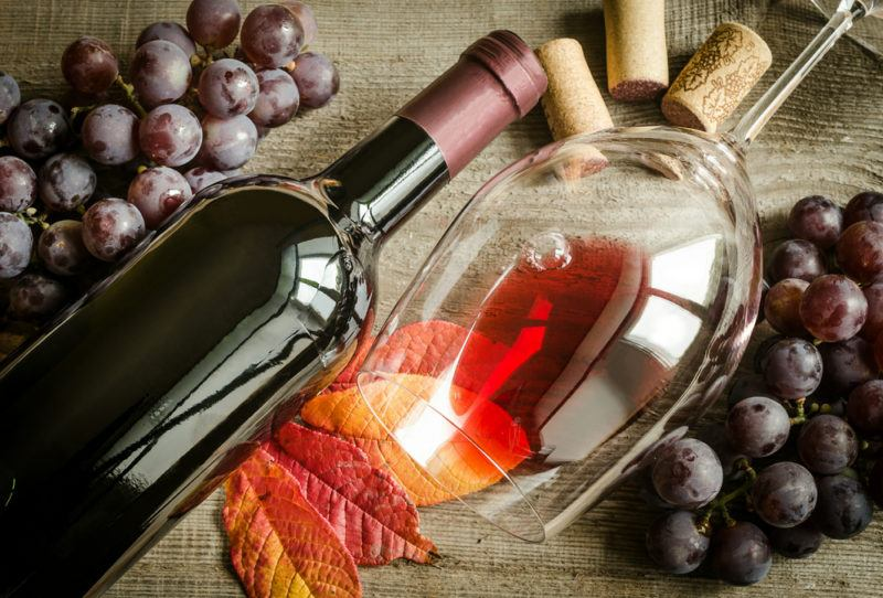 A bottle of pinot noir, a glass with a little wine in it, an autumn leaf, two bunches of grapes and some wine corks