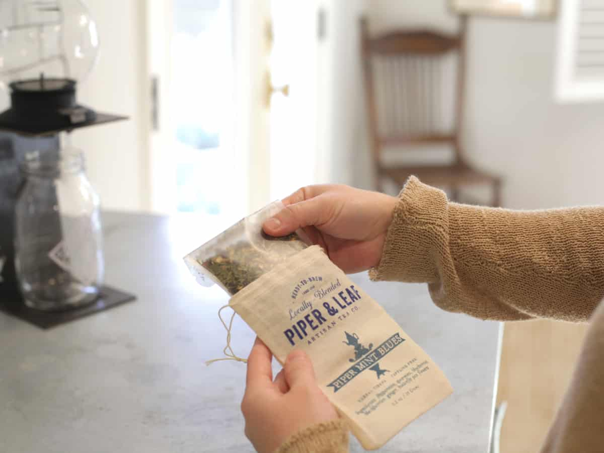 Person's hands and forearms on the right side of the photo holding pouch of tea with bag that states Piper and leaf, Piper Mint Blues. Background is a kitchen counter